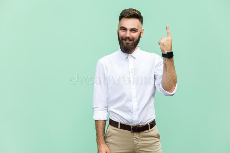 De jonge volwassen zakenman heeft een idee, die met vinger richten omhoog op lichtgroene muurachtergrond wordt geïsoleerd stock afbeeldingen