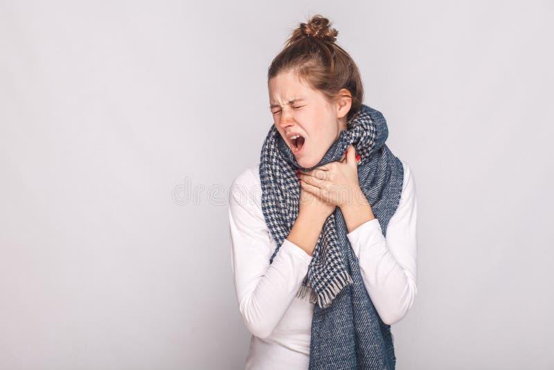 De jonge volwassen zieke vrouw wat betreft haar hals, heeft hoest, pijnlijke throa royalty-vrije stock afbeelding