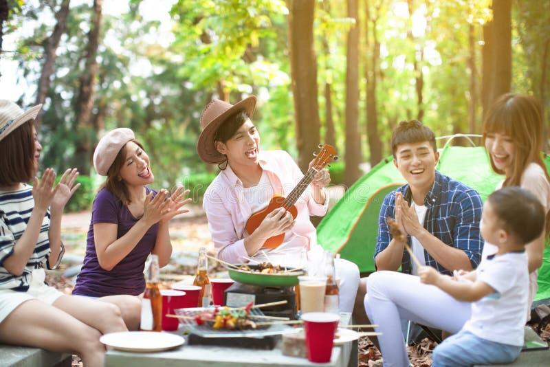 de jonge vrienden groeperen het genieten van picknick van partij en het kamperen stock afbeelding