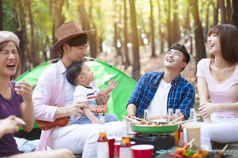 de jonge vrienden groeperen het genieten van picknick van partij en het kamperen royalty-vrije stock foto