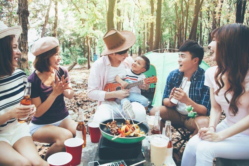 de jonge vrienden groeperen het genieten van picknick van partij en het kamperen royalty-vrije stock foto's