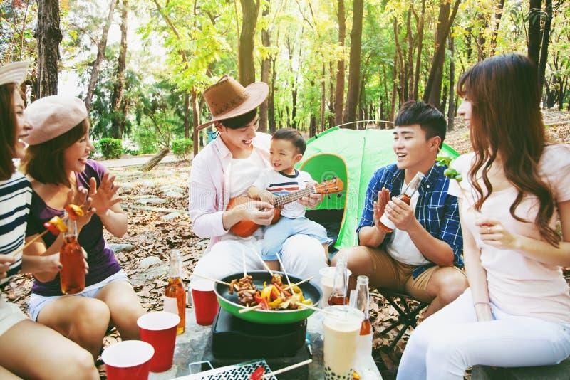 de jonge vrienden groeperen het genieten van picknick van partij en het kamperen royalty-vrije stock afbeelding