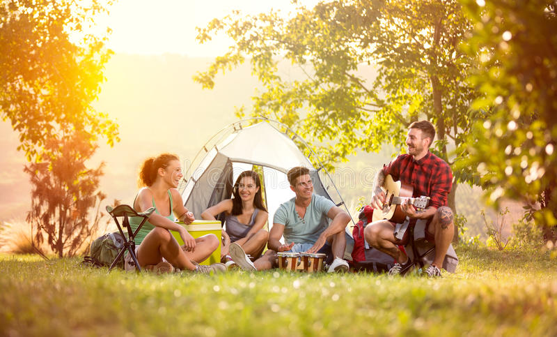 De jonge vrienden hebben goede tijd op het kamperen reis royalty-vrije stock foto's