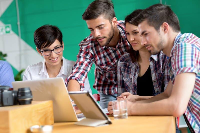 De jonge vrienden met laptop in koffie winkelen royalty-vrije stock afbeelding