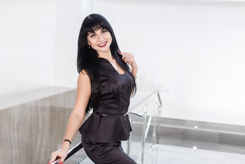 De jonge vrij gelukkige donkerbruine vrouw gekleed in een zwart pak met een korte rok bevindt zich tegen de witte muur in bureau royalty-vrije stock afbeeldingen