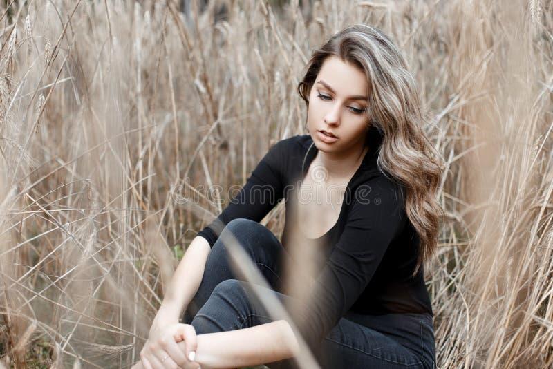 De jonge vrij leuke vrouw in modieuze jeans in in zwarte t-shirt rust zitting op de grond op het gebied stock fotografie