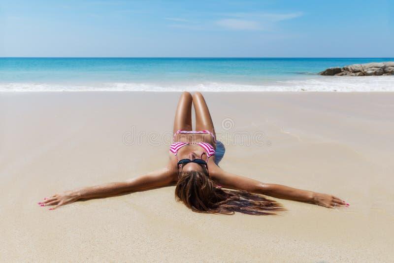 De jonge vrij slanke donkerbruine vrouw in zonnebril zonnebaadt op strand stock afbeelding