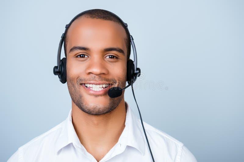 De jonge vrolijke Afrikaanse arbeider van het kerelcall centre in hoofdtelefoon op pu royalty-vrije stock afbeeldingen