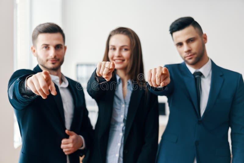 De jonge vrolijke bedrijfsmensen richten vinger op u stock foto