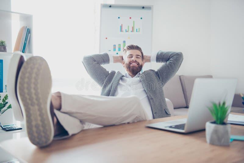 De jonge vrolijke zakenman rust op het werk, met voeten royalty-vrije stock foto