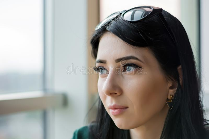 De jonge vrouw in anticiperen kijkt uit het reusachtige venster aan de straat royalty-vrije stock fotografie