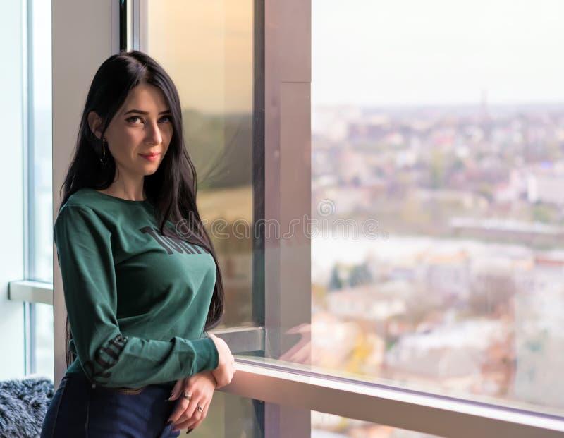 De jonge vrouw in anticiperen kijkt uit het reusachtige venster aan de straat royalty-vrije stock foto's