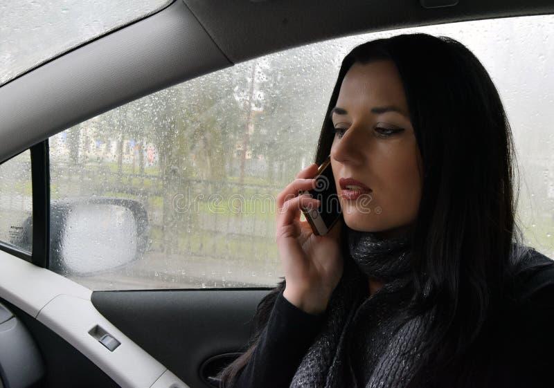 De jonge vrouw is in de auto stock afbeeldingen