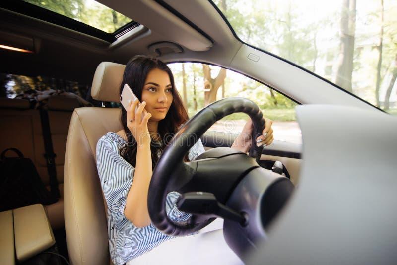 De jonge vrouw is in de auto Het jonge Vrouwen mooie brunette spreekt door de mobiele telefoon stock afbeeldingen