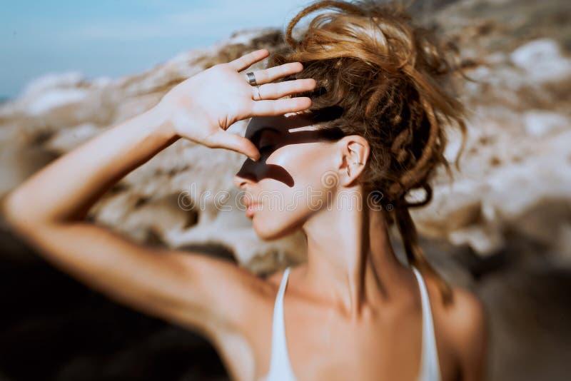 De jonge vrouw behandelt haar gezicht in openlucht met hand De foto was genomen w royalty-vrije stock foto