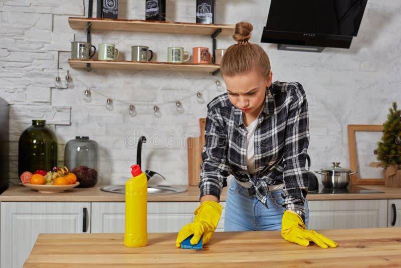 De jonge vrouw in beschermende handschoenen veegt een lijst in de keuken met een vod af stock afbeeldingen