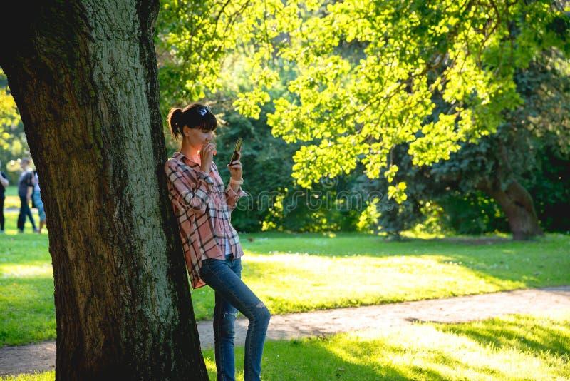 De jonge vrouw bevindt zich onder een boom met een telefoon indient binnen Th stock afbeeldingen