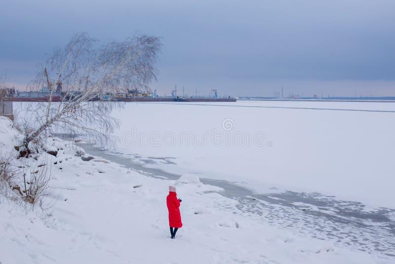 De jonge vrouw bevindt zich op bank van bevroren rivier en bekijkt schilderlandschap stock fotografie