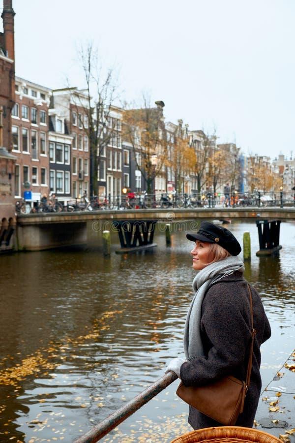 De jonge vrouw bevindt zich op de brug en bekijkt het kanaal van Amsterdam, Nederland royalty-vrije stock foto's