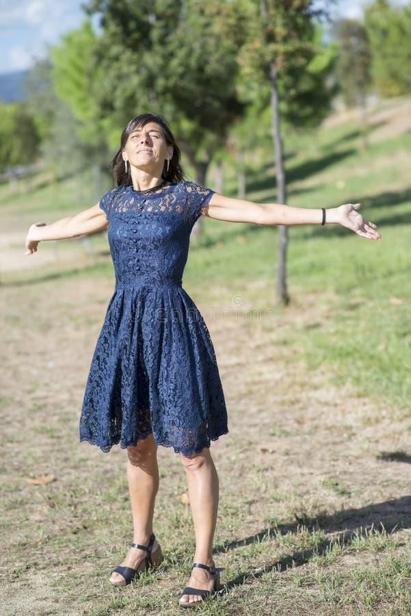 De jonge vrouw bewapent opgeheven genietend van de verse lucht in groen bos stock afbeeldingen