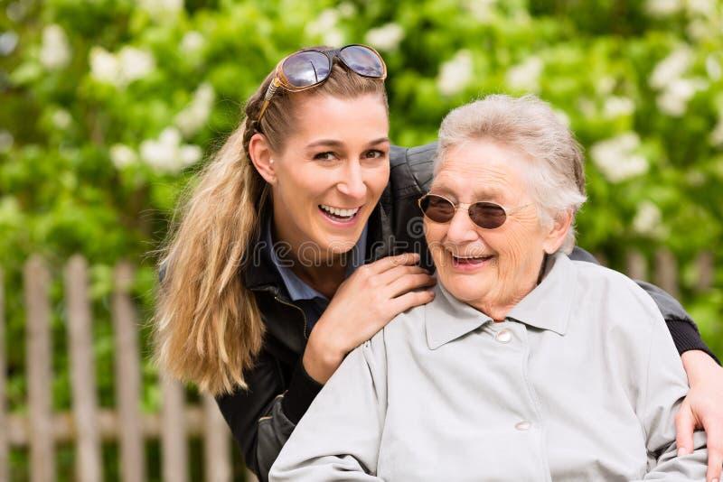 De jonge vrouw bezoekt haar grootmoeder in verpleeghuis stock afbeeldingen