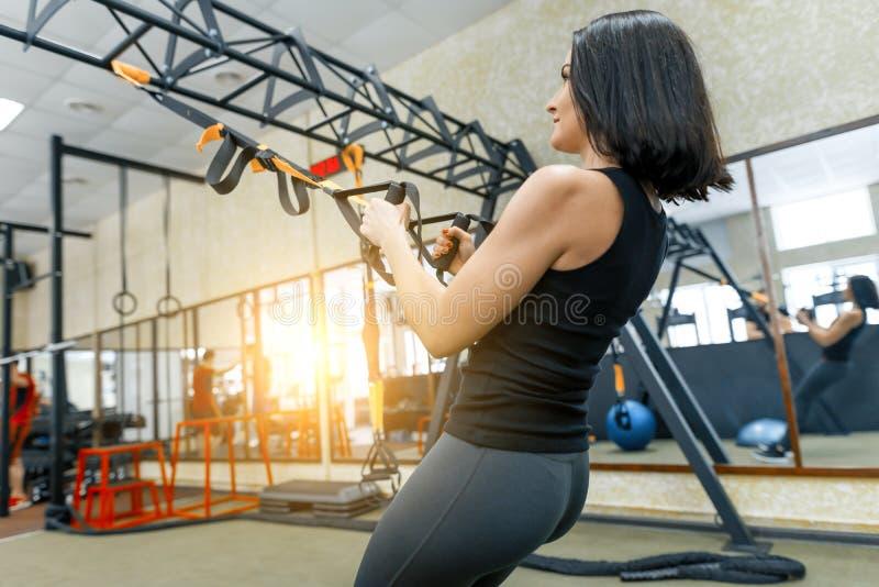 De jonge vrouw bij de gymnastiek die fitness oefeningen doen die sporten gebruiken bindt systeem vast, die handen houden door de  stock foto