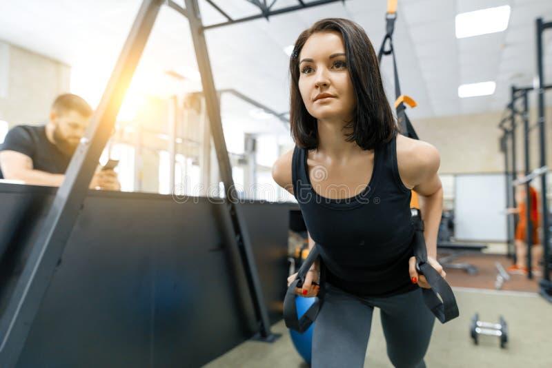 De jonge vrouw bij de gymnastiek die fitness oefeningen doen die sporten gebruiken bindt systeem vast, die handen houden door de  stock afbeeldingen