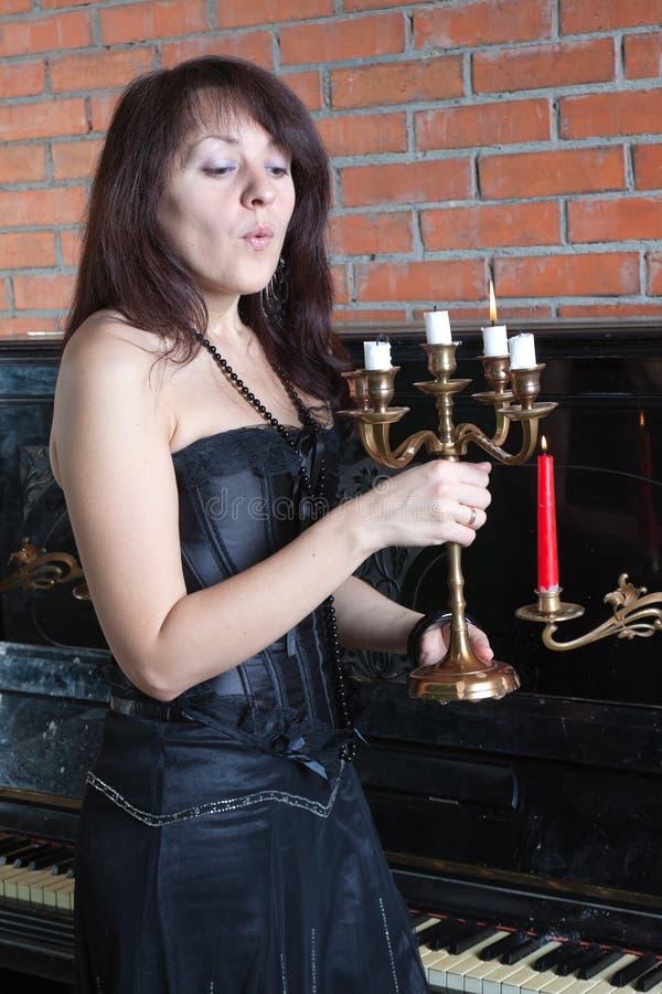 De jonge vrouw blaast uit kaarsen royalty-vrije stock afbeelding