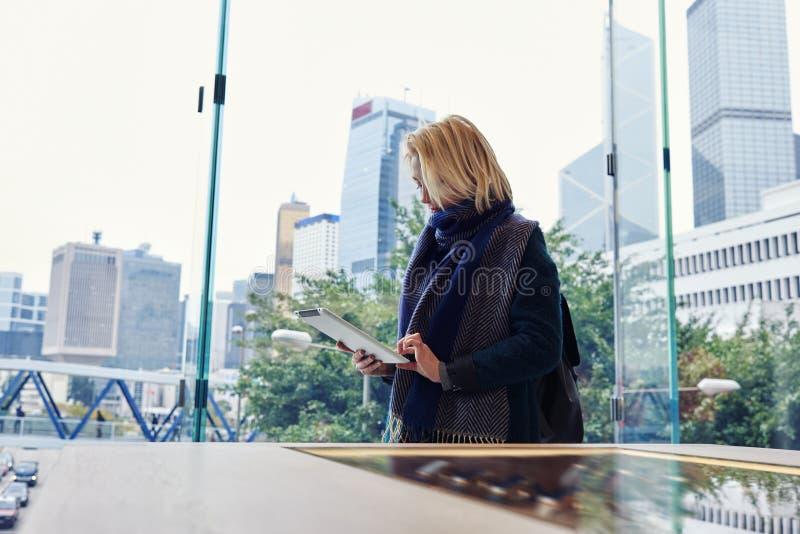 De jonge vrouw boekt hotel via digitale tablet tijdens haar bedrijfsreis stock afbeeldingen
