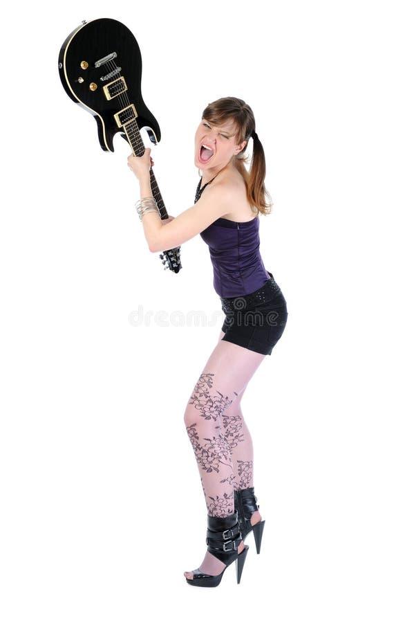 De jonge vrouw breekt de gitaar. stock afbeeldingen