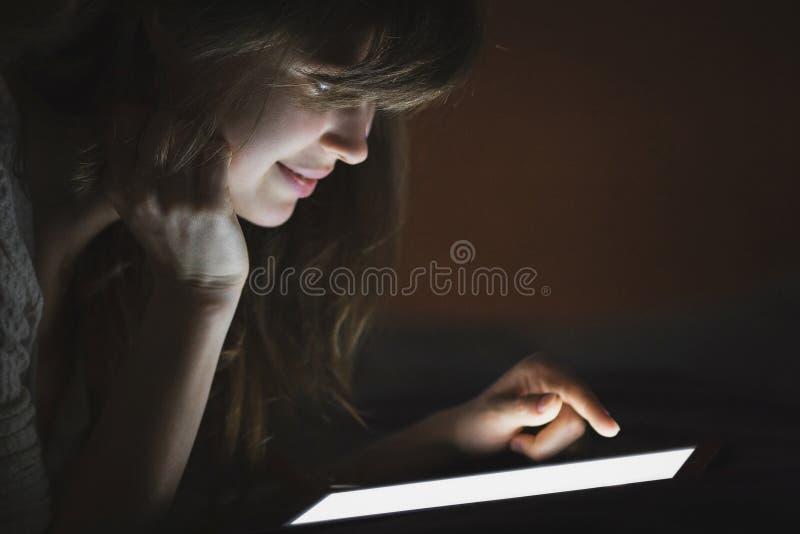 de jonge vrouw brengt tijd in de avond aan Internet, het technologieconcept en het vermaak door royalty-vrije stock foto's