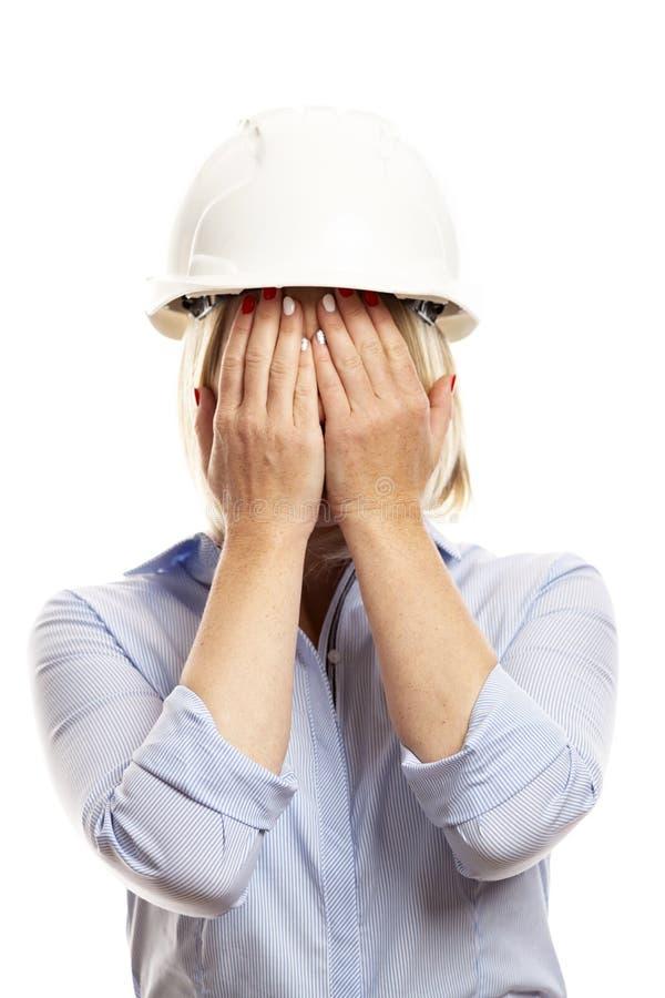 De jonge vrouw in bureaukleren en een bouwhelm behandelden haar gezicht met haar handen Witte achtergrond stock fotografie