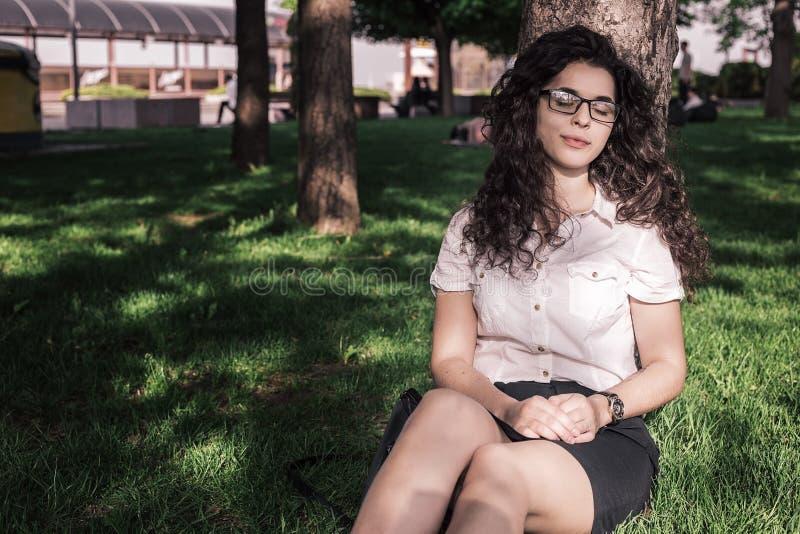 De jonge vrouw in bureaukleren krijgt rust in park royalty-vrije stock afbeeldingen