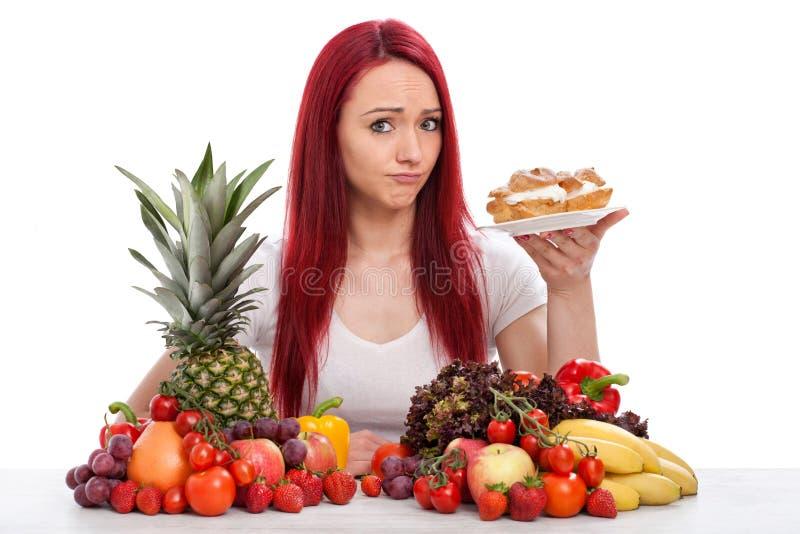 De jonge vrouw denkt over het eten van een cake eerder dan vruchten of groenten stock fotografie