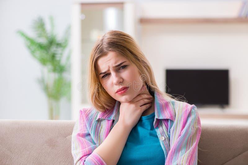 De jonge vrouw die aan keelpijnpijn lijden stock foto's