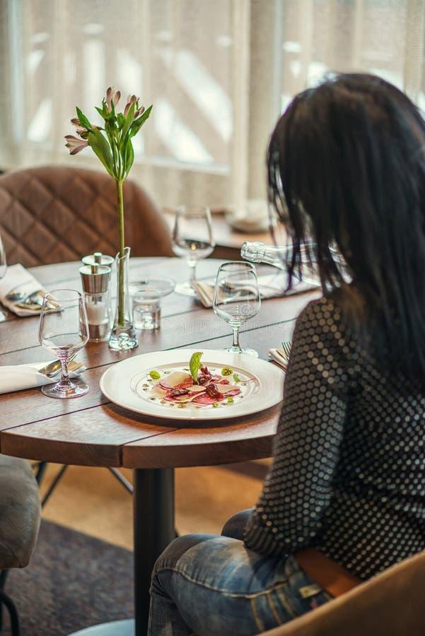 De jonge vrouw die carpaccio van rundvleesfilet eten diende op witte plaat met parmezaanse kaas, pesto en kruiden, productfotogra royalty-vrije stock foto