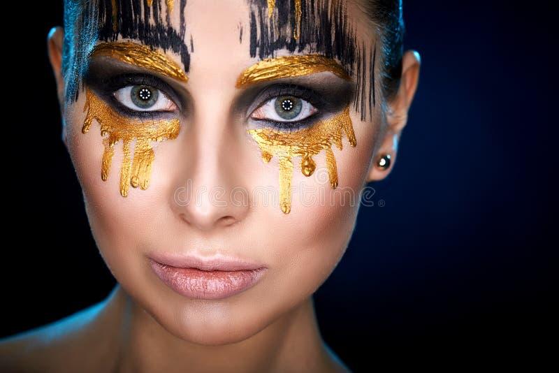 De jonge vrouw die de camera met fantasie bekijken maakt omhoog de studioschot van de gezichtskunst royalty-vrije stock foto