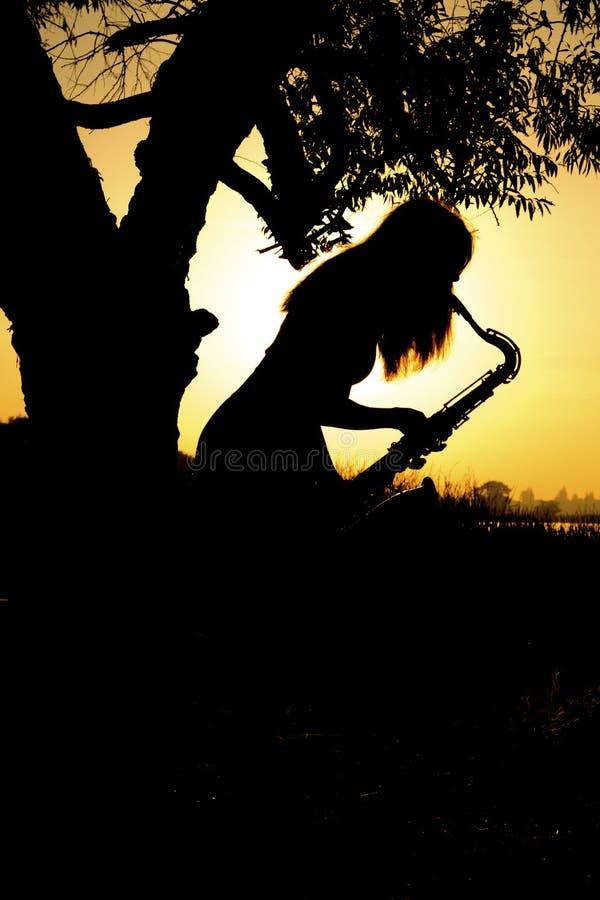 De jonge vrouw die de saxofoon spelen die op een boom leunen is dichtbij een rivier in de achtergrondzonsopgang stock afbeeldingen