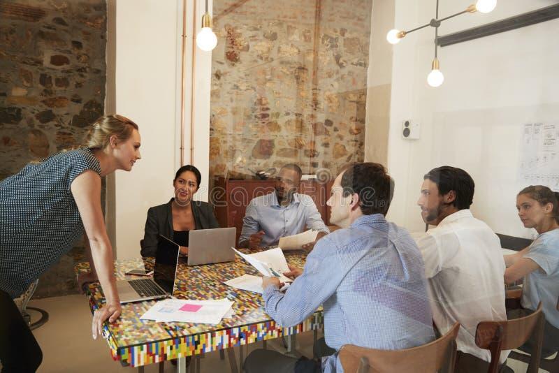 De jonge vrouw die een teamvergadering in een bestuurskamer beheren, sluit omhoog stock foto