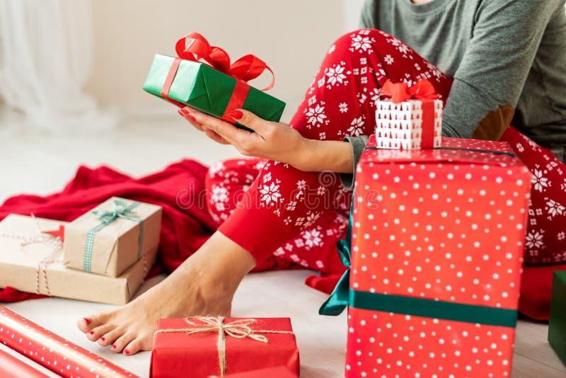 De jonge vrouw die Kerstmispyjama's dragen die op de vloer onder verpakte Kerstmis zitten stelt, het ontspannen voor royalty-vrije stock fotografie