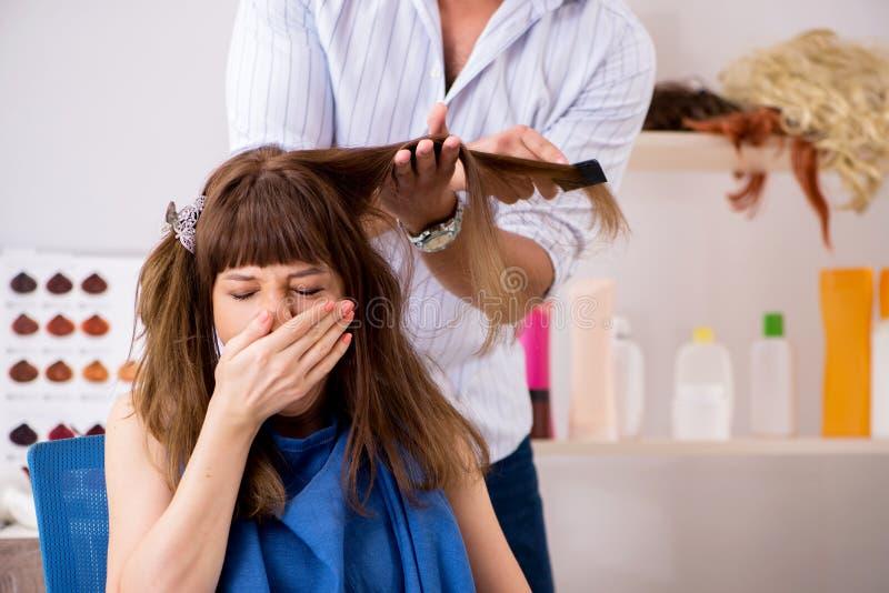 De jonge vrouw die jonge knappe kapper bezoeken stock foto's