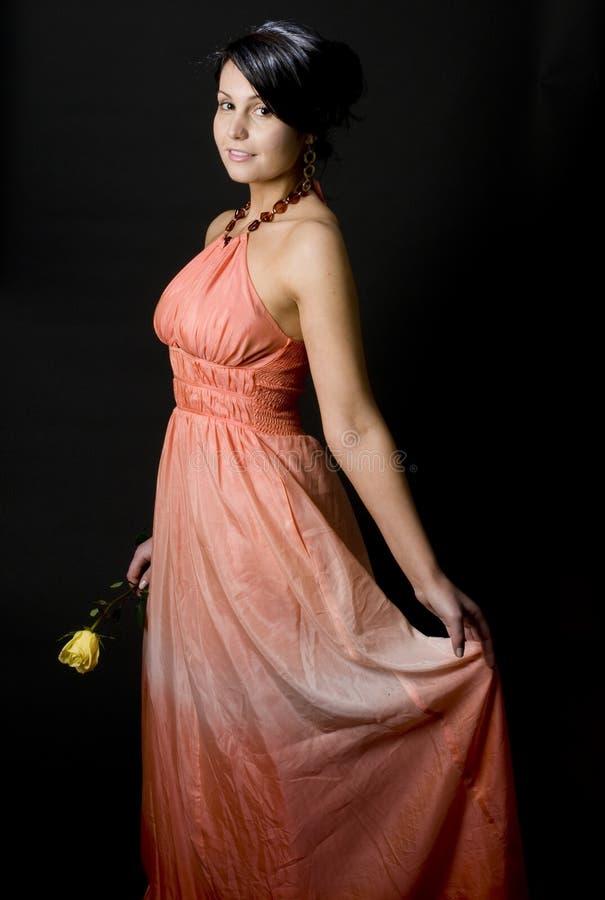 De jonge vrouw die mooie kleding glimlacht met nam toe stock foto's
