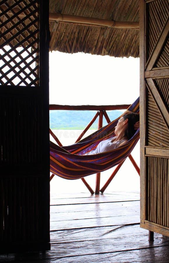 De jonge vrouw die op een hangmat in Yandup-Eiland rusten brengt, Panama onder stock fotografie