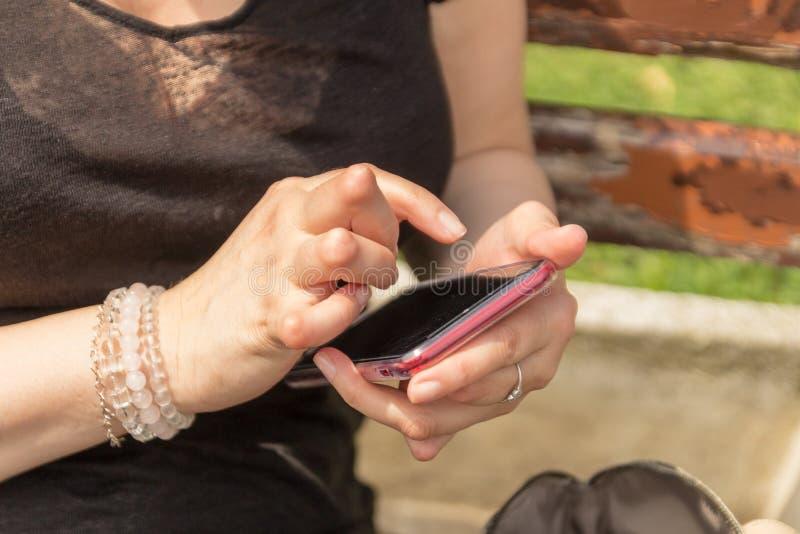 De jonge vrouw die reumatoïde artritis hebben neemt een rust zitting op een bank, bekijkend haar telefoon bij een park royalty-vrije stock foto's