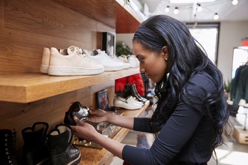 De jonge vrouw die schoenen op vertoning in een winkel bekijken, sluit omhoog stock foto's