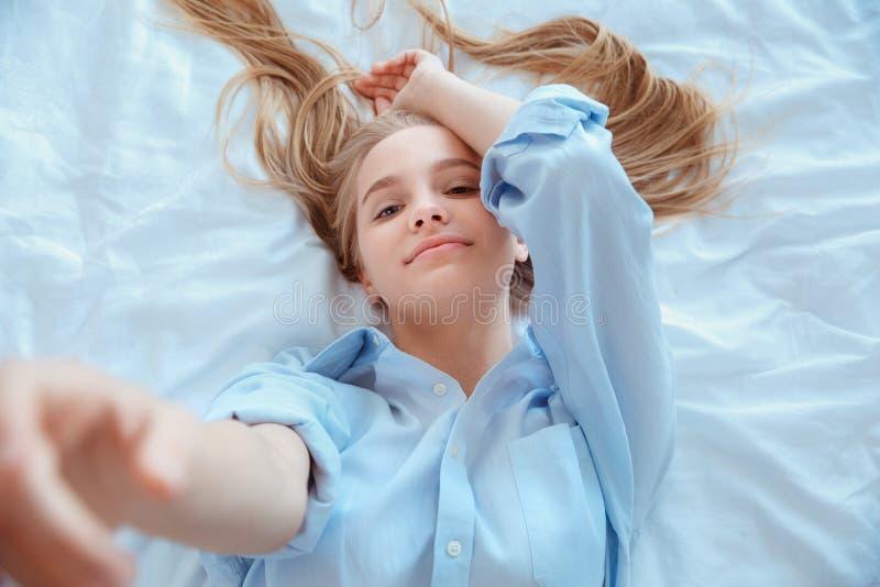 De jonge vrouw die thuis in bed leggen wekte hoogste mening wat betreft camera royalty-vrije stock afbeeldingen