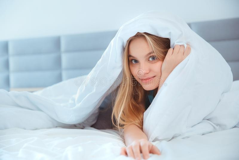 De jonge vrouw die thuis in bed leggen wekte omhoog het verbergen onder deken royalty-vrije stock afbeelding