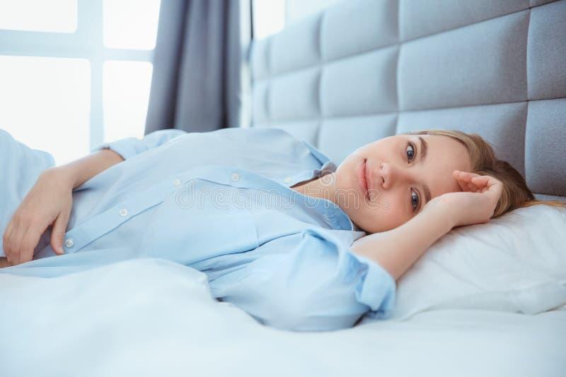 De jonge vrouw die thuis in bed leggen wekte slaperig royalty-vrije stock fotografie