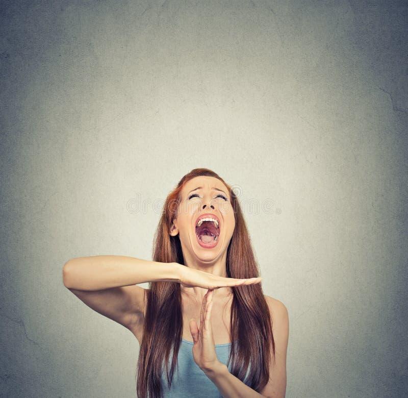 De jonge vrouw die tijd tonen overhandigt uit gebaar, het gefrustreerde gillen royalty-vrije stock fotografie
