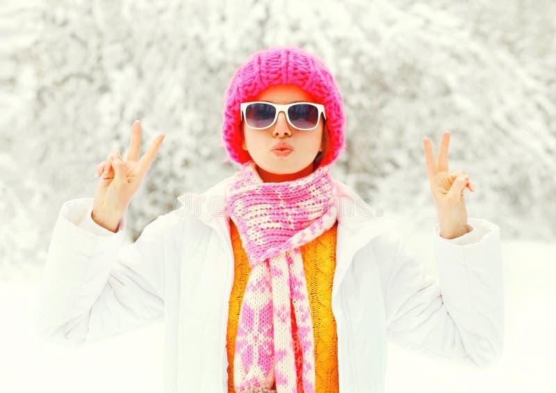 De jonge vrouw die van de manierwinter kleurrijke gebreide hoed, sjaal dragen die pret over sneeuw bosparkachtergrond hebben stock foto's
